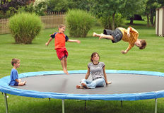 Kids on Trampoline. Four children having a great time jumping on trampoline, motion stock image