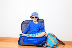 Kids travel concept- little boy sitting on packed suitcase Stock Photo