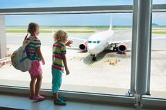 Kids travel and fly. Child at airplane in airport. Kids at airport. Children look at airplane. Traveling and flying with child. Family at departure gate stock images