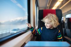 Kids travel by train. Railway trip with child. Child traveling by train. Little kid in a high speed express train on family vacation in Europe. Travel by royalty free stock image