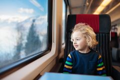 Kids travel by train. Railway trip with child. Child traveling by train. Little kid in a high speed express train on family vacation in Europe. Travel by stock photography