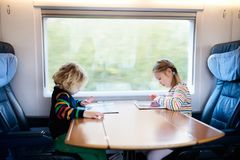 Kids travel by train. Railway trip with child. Child traveling by train. Little kid in a high speed express train on family vacation in Europe. Travel by royalty free stock photo