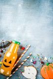 Kids treats for Halloween. Funny homemade glazed cookies, various candies milk and juice in monster bottle, blue concrete background copy space top view royalty free stock photo