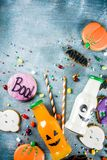 Kids treats for Halloween. Funny homemade glazed cookies, various candies milk and juice in monster bottle, blue concrete background copy space top view stock photos