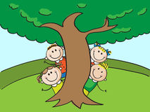 Kids and tree. Four kids hiding behind tree Royalty Free Stock Images