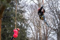 Kids in a tree harness learn about safety. March 17, 2019  New Carlisle Indiana USA; kids in a tree harness learn about safety from tree workers during the Sugar royalty free stock photography