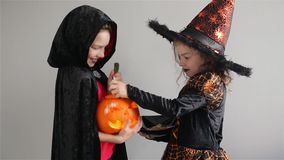 Kids trick or treat. Boy and girl in suits for HalloweenGirl holds sweets in hands. Boy holds pumpkin with a candle stock video