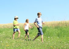 Kids on trip. Three kids - two boys and one girl walking on meadow with Stock Photos