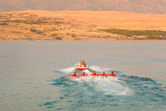 Kids tube riding tawed by speedboat. Stock Images