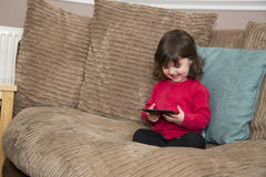 Kids TV on a tablet. Young girls watching Kids TV on a tablet Royalty Free Stock Images