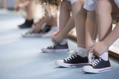 Kids tying sport shoes close-up. Close-up on school kids` legs while they`re sitting on a bench and tying their sport shoes for physical education activities royalty free stock photography