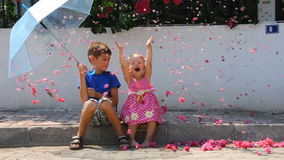 Kids with umbrella and flowers. Youn boy and little girl with umbrella and flowers stock video