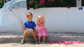 Kids with umbrella and flowers. Youn boy and little girl with umbrella and flowers stock footage