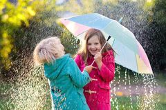 Kids with umbrella playing in autumn shower rain