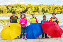 Kids with umbrellas. Kids in rubber boots stand on the autumn beach behind umbrellas Royalty Free Stock Images