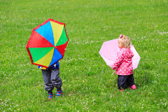 Kids with umbrellas outdoors on rainy day Stock Image