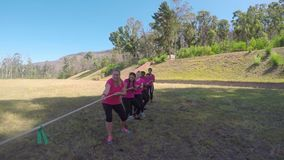 Kids in uniform playing tug of war during obstacle course 4k. Kids in uniform playing tug of war during obstacle course on a sunny day 4k stock footage