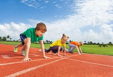 Kids in uniforms on bended knee ready to run stock images