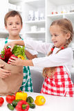 Kids unpacking vegetables in the kitchen Royalty Free Stock Images