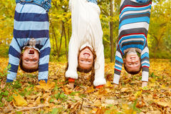 Kids upside down. Three kids upside down in autumn park royalty free stock photo