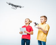 Kids using digital tablet and hexacopter drone. Happy kids using digital tablet and hexacopter drone isolated on white royalty free stock photography