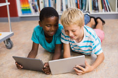 Kids using digital tablet in library. Kids lying on floor using digital tablet in library Royalty Free Stock Photo
