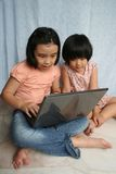 Kids using laptop. Two little girls looking and using the laptop Stock Image