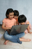 Kids using laptop. Kids sitting on the floor using and learning laptop Royalty Free Stock Images