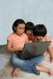 Kids using laptop. Kids sitting on the floor using and learning laptop Stock Image