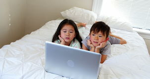 Kids using laptop on bed. In bedroom stock footage