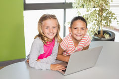 Kids using laptop in library Stock Photography