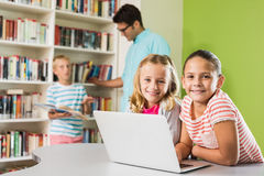 Kids using laptop in library Stock Images