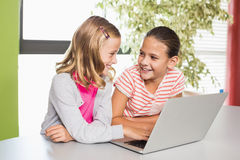 Kids using laptop in library Royalty Free Stock Photos
