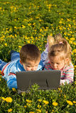 Kids using laptop on the spring flower field Stock Photo