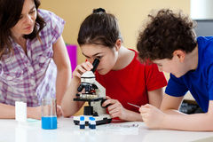 Kids using microscope royalty free stock image