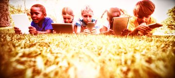 Kids using technology during a sunny day stock image