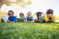 Kids using technology during a sunny day. At park Stock Photo