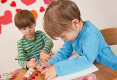 Kids Valentine's Day Crafts: Love and Hearts. Kids, children, doing Valentine's day arts and crafts with hearts, pencils, paper, love concept royalty free stock photo