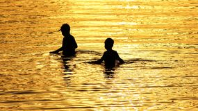 Kids wading in water at sunset Stock Image