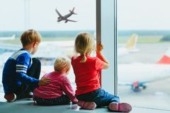 Kids waiting for plane in airport, family travel. Kids wait looking at planes in airport, family travel concept royalty free stock images