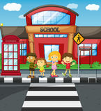 Kids waiting to cross the road in front of school Royalty Free Stock Photography