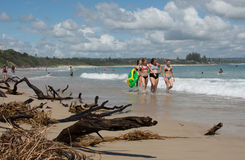 Kids walk in the beach of Byron Bay. Stock Photos