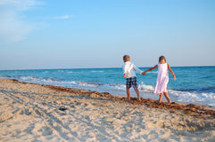 Kids walking along the beach together Stock Image