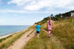 Kids walking along the coastline Stock Image