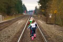 Kids walking down train tracks Stock Images
