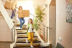 Kids walking downstairs. Little girl carrying a box Stock Photography