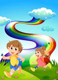 Kids walking at the hill with a rainbow in the sky Royalty Free Stock Photography