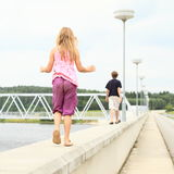 Kids walking on railing of dam Royalty Free Stock Images