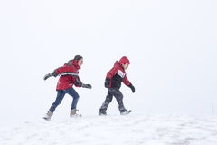 Kids walking while snowing. Stock Photography