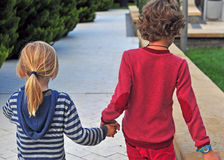 Kids walking by street hand by hand Royalty Free Stock Photo